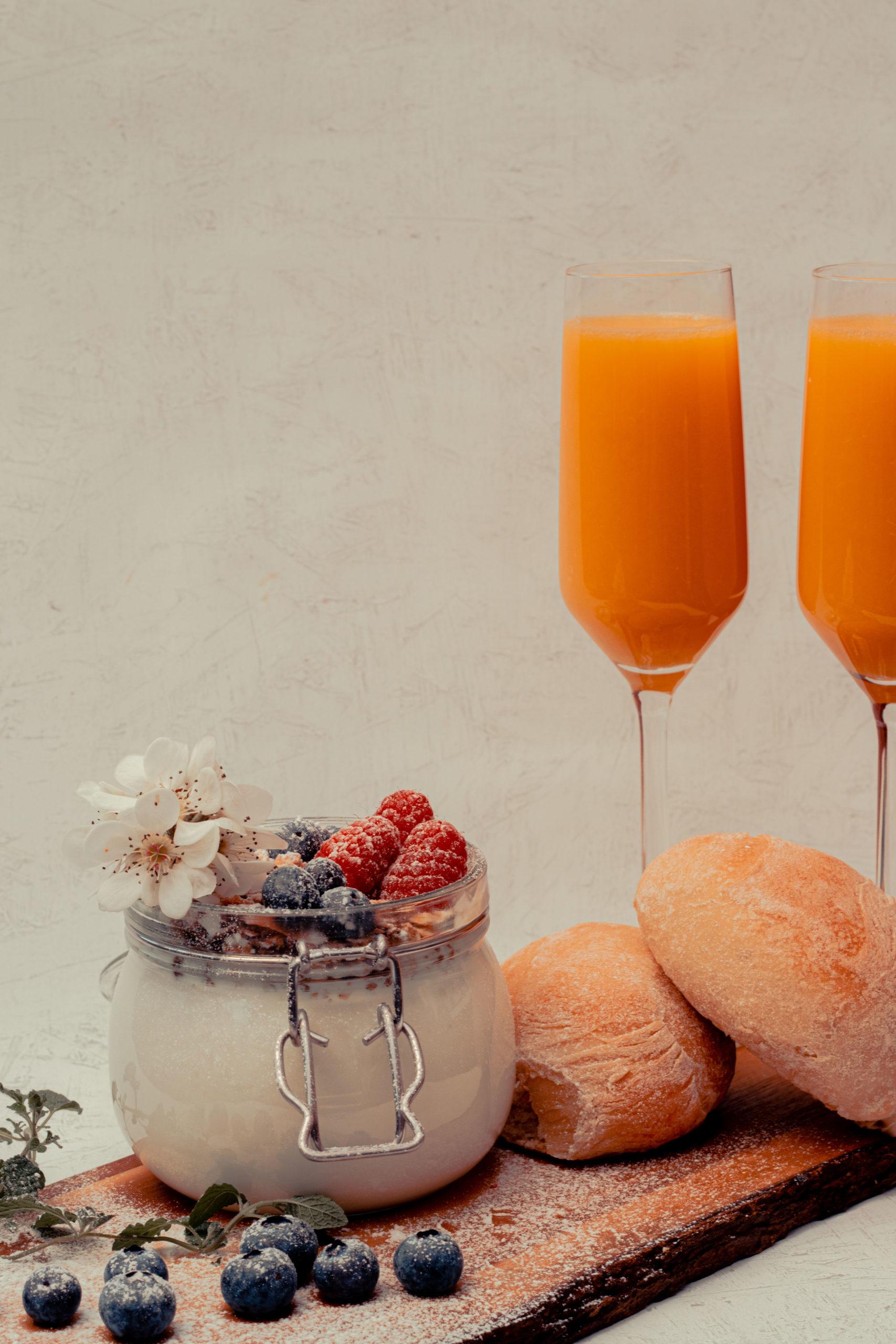 brunch, breakfast, orangejuice, buns, blueberrys, raspberrys, bowl with yoghurt and musli on a platter, mimosas